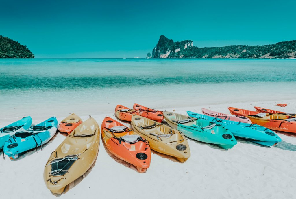 picture of kayaks on a sandy beach with crystal turquoise waters. EverydayKayaker.com features kayaking destinations, kayaking tips and tricks, and resources for kayakers!